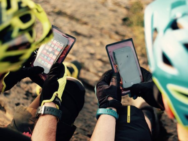 Over Shoulder View of Mountain Bikers Using Phone Wallet